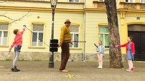 Cuerda del viejo hombre que salta con tres muchachas almacen de metraje de vídeo