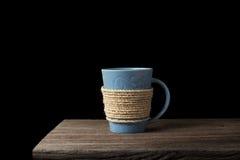 Cuerda envuelta alrededor de la taza de café en el escritorio de madera Imágenes de archivo libres de regalías