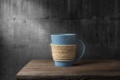 Cuerda envuelta alrededor de la taza de café en el escritorio de madera Fotografía de archivo