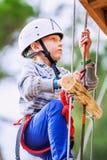 Cuerda-escalera que sube del muchacho en parque de la adrenalina Foto de archivo