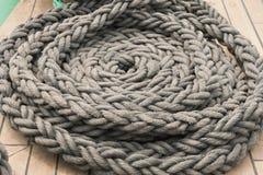 Cuerda gris del mar, doblada en un primer del círculo en la cubierta del ` s de la nave fotos de archivo libres de regalías