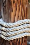 Cuerda gruesa alrededor de un bolardo de madera del amarre, Croacia Imagen de archivo libre de regalías