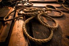Cuerda gruesa del coco en la cubierta de madera del barco de pesca Fotografía de archivo