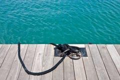 Cuerda negra atada para planchar los anillos en el borde de un muelle Fotografía de archivo libre de regalías
