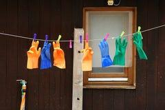 Cuerda para tender la ropa con los guantes coloreados fijados con las clavijas coloreadas Imágenes de archivo libres de regalías