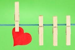 Cuerda para tender la ropa con un corazón rojo Imagen de archivo