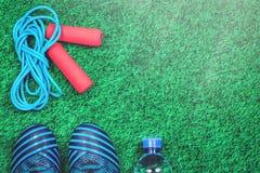 Cuerda que salta, botella de agua y listones contra césped artificial verde imagenes de archivo