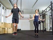 Cuerda que salta de la mujer y del hombre en el gimnasio Imagen de archivo