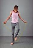 Cuerda que salta del adolescente muscular joven sano en estudio Niño que ejercita con el salto arriba en fondo gris Imagen de archivo libre de regalías