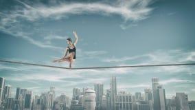 Cuerda tirante del gimnasta sobre ciudad Imágenes de archivo libres de regalías