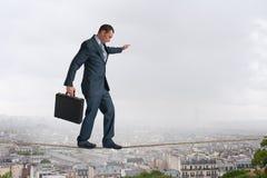 Cuerda tirante que camina del hombre de negocios sobre ciudad Imagen de archivo