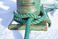 Cuerda verde anudada alrededor de un bolardo Imagenes de archivo