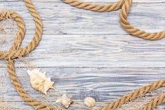 Cuerda y cáscara marinas en los tableros blancos Imagen de archivo