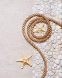Cuerda y estrellas de mar en el arena de mar Foto de archivo