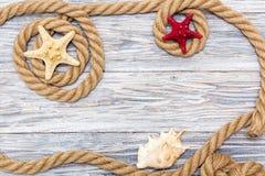 Cuerda y estrellas de mar marinas en los tableros blancos Foto de archivo