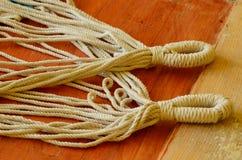 Cuerdas con los lazos en fondo de madera Fotos de archivo libres de regalías