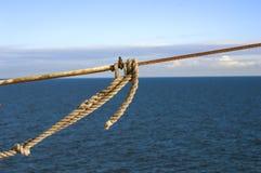 Cuerdas de la nave con un nudo en fondo azul del mar fotografía de archivo