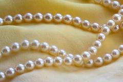 Cuerdas de rosca de las perlas en una tela amarilla. Foto de archivo