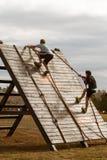 Cuerdas del uso de la gente para subir la pared en raza de obstáculo extrema Foto de archivo libre de regalías