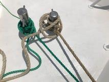 Cuerdas fuertes blancas y verdes de la nave de la tela, cuerdas atadas a una nave, un barco en un fondo blanco foto de archivo libre de regalías