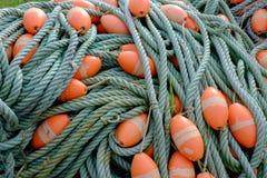 Cuerdas verdes de la red de pesca con los flotadores anaranjados foto de archivo