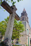 Cuernavaca Cathedral. A cross and the single long tower of the imposing austere stone cathedral. Cuernavaca, Morelos, Mexico royalty free stock photography