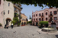 Cuernavaca Plaza Mexico. A typical plaza in Cuernavaca, Mexico. A stone street, a fountain, historical colorful buildings with overhanging balconies and iron Royalty Free Stock Photography