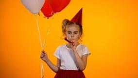 Cuerno del partido de la muchacha sola infeliz y globos el sostenerse que soplan que celebran cumpleaños foto de archivo libre de regalías