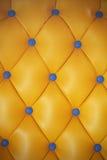 Cuero artificial amarillo y botón azul Imagen de archivo