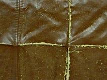 cuero sintético de la grieta marrón, lona dañada de la tela de cuero vieja del fondo vieja con las costuras rectas imágenes de archivo libres de regalías
