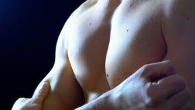 Cuerpo atractivo de un atleta de sexo masculino muscular Flexing Muscles en un fondo negro almacen de metraje de vídeo