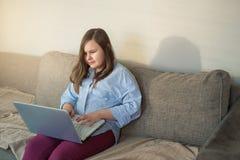 Cuerpo completo del adolescente hermoso que trabaja detrás del ordenador portátil Imagenes de archivo