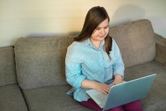 Cuerpo completo del adolescente hermoso que trabaja detrás del ordenador portátil Fotos de archivo libres de regalías
