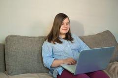 Cuerpo completo del adolescente hermoso que trabaja detrás del ordenador portátil Foto de archivo