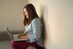 Cuerpo completo del adolescente hermoso que trabaja detrás del ordenador portátil Fotografía de archivo libre de regalías