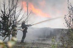 Cuerpo de bomberos en la acción durante almacenes ardientes con los productos plásticos Fotografía de archivo libre de regalías