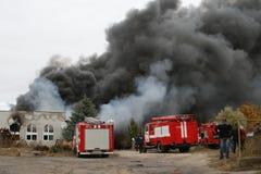 Cuerpo de bomberos en la acción durante almacenes ardientes con los productos plásticos Foto de archivo libre de regalías