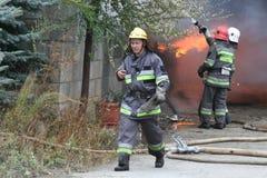 Cuerpo de bomberos en la acción durante almacenes ardientes con los productos plásticos Imagen de archivo libre de regalías
