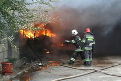 Cuerpo de bomberos en la acción durante almacenes ardientes con los productos plásticos Imagen de archivo