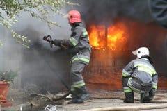 Cuerpo de bomberos en la acción durante almacenes ardientes con los productos plásticos Foto de archivo