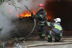Cuerpo de bomberos en la acción durante almacenes ardientes con los productos plásticos Fotografía de archivo