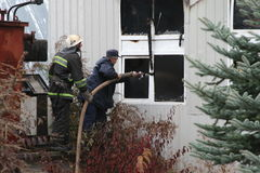 Cuerpo de bomberos en la acción durante almacenes ardientes con los productos plásticos Imágenes de archivo libres de regalías