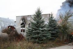 Cuerpo de bomberos en la acción durante almacenes ardientes con los productos plásticos Imagenes de archivo