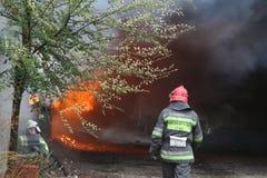 Cuerpo de bomberos en la acción durante almacenes ardientes con los productos plásticos Fotos de archivo