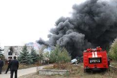 Cuerpo de bomberos en la acción durante almacenes ardientes con los productos plásticos Fotos de archivo libres de regalías