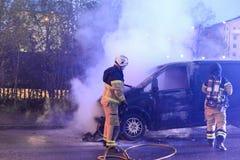 Cuerpo de bomberos que apaga el fuego del coche Imágenes de archivo libres de regalías