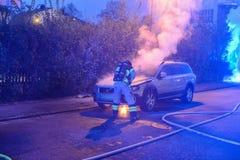 Cuerpo de bomberos que apaga el fuego del coche Fotografía de archivo libre de regalías