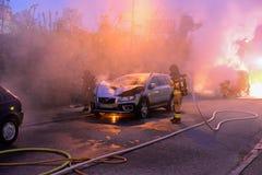 Cuerpo de bomberos que apaga el fuego del coche Fotografía de archivo