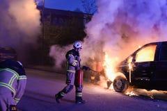 Cuerpo de bomberos que apaga el fuego del coche Imagen de archivo libre de regalías
