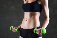 Cuerpo de las pesas de gimnasia de elevación de la mujer apta de los jóvenes Foto de archivo